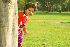Adorable happy kid with curly hair peeking around the tree. Playing hide and seek in a park at summer evening stock images