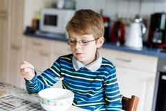 Happy little blond kid boy eating cereals for breakfast or lunch. Healthy eating for children. Stock Photography