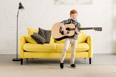 Adorable happy little boy playing guitar. At home stock photo