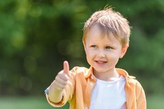 Adorable happy little boy showing thumb up. In park stock image