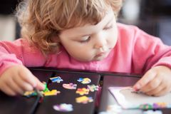 Adorable happy little child playing with puzzle. stock images