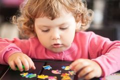 Adorable happy little child playing with puzzle. stock photography