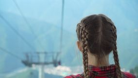Adorable happy little girl in the cabin on the cable car in mountains in the background of beautful landscape stock footage