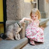 Adorable happy little girl and a cat. Outdoors Stock Photos