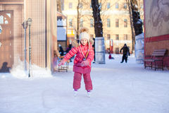 Adorable happy little girl enjoying skating at the Stock Images