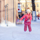 Adorable happy little girl enjoying skating at the Royalty Free Stock Photo
