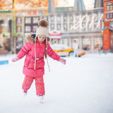 Adorable happy little girl enjoying skating at the Royalty Free Stock Photography
