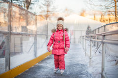 Adorable happy little girl enjoying skating at the Stock Photography