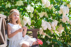 Adorable happy little girl in flower blossoming Stock Photo