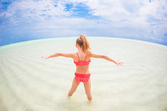 Adorable happy little girl have fun at shallow water on beach vacation Royalty Free Stock Image