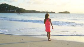 Adorable happy little girl hvaing fun on white beach at sunset. SLOW MOTION VIDEO stock footage