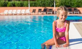 Adorable happy little girl in the swimming pool Stock Photos