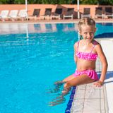 Adorable happy little girl in the swimming pool. Cute little girl in the swimming pool looks at camera Royalty Free Stock Photos