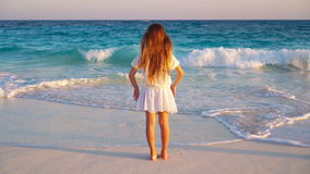 Adorable happy little girl on tropical beach at sunset light. Adorable little girl at beach during summer vacation stock footage