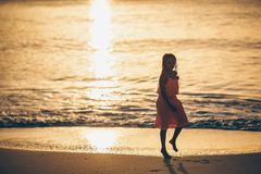 Adorable happy little girl on white beach at sunset. stock photography