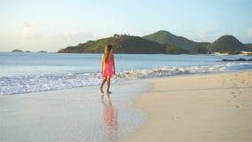 Adorable happy little girl walking on white beach. stock video