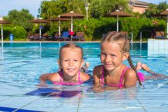 Adorable happy little girls having fun in the. Cute little girls in the swimming pool looks at camera Stock Photos