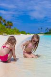 Adorable happy little girls at shallow water on Stock Photography