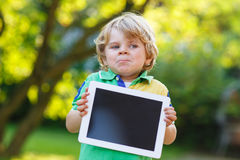 Adorable happy little kid boy holding tablet pc, outdoors Royalty Free Stock Photos