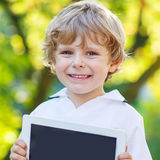 Adorable happy little kid boy holding tablet pc, outdoors Stock Photo
