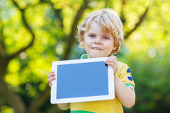 Adorable happy little kid boy holding tablet pc, outdoors Stock Photos