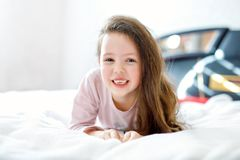 Adorable happy little kid girl with long hairs after sleeping in his white hotel bed in colorful nightwear. School child stock photos