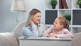 Adorable happy mother helping little pupil teen daughter doing homework enjoying motherhood stock video footage