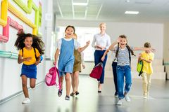 Adorable happy schoolchildren running by school corridor together with teacher. Walking behind royalty free stock photos