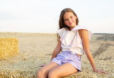 Free Adorable Happy Smiling Ittle Girl Child Sitting On A Hay Rolls In A Wheat Field Stock Photos - 195339613