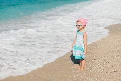 Adorable happy smiling little girl with curly hair on beach vaca Stock Photos