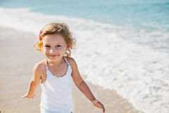 Adorable happy smiling little girl with curly hair on beach vaca Stock Photo