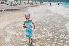 Adorable happy smiling little girl with curly hair on beach vaca Royalty Free Stock Photo