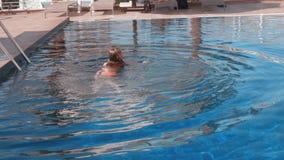 Adorable happy teenage girl swimming in outdoor pool stock video
