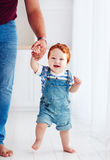 Adorable happy toddler boy walking with the help of the father Stock Images