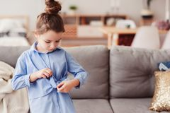 Adorable happy 5 years old child girl checking bow on her fashion shirt. At home Royalty Free Stock Photos