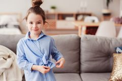 Adorable happy 5 years old child girl checking bow on her fashion shirt. At home Royalty Free Stock Image