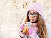 Adorable happy young blonde woman in pink knitted hat scarf having fun drinking hot tea from mug snowy winter park forest in natur Royalty Free Stock Images