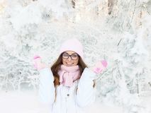 Adorable happy young blonde woman in pink knitted hat scarf having fun snowy winter park forest in nature Royalty Free Stock Images