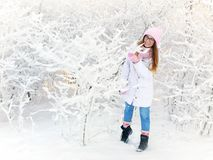 Adorable happy young blonde woman in pink knitted hat scarf having fun snowy winter park forest in nature Stock Photos