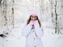 Adorable happy young blonde woman in pink knitted hat scarf having fun strolling snowy winter forest in nature Royalty Free Stock Photography