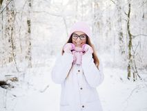 Adorable happy young blonde woman in pink knitted hat scarf having fun strolling snowy winter forest in nature Royalty Free Stock Photo