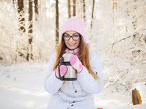 Adorable happy young blonde woman in pink knitted hat scarf having fun strolling snowy winter park forest in nature Royalty Free Stock Images