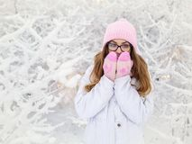 Adorable happy young blonde woman in pink knitted hat scarf mittens having fun snowy winter park forest sunny day in nature Royalty Free Stock Photos