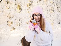 Adorable happy young blonde woman in pink knitted hat scarf having fun drinking hot tea from mug snowy winter park forest in natur Stock Photos