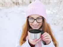 Adorable happy young blonde woman in pink knitted hat scarf having fun drinking hot tea from thermos cup snowy winter park forest Stock Photo