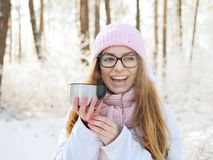 Adorable happy young blonde woman in pink knitted hat scarf having fun drinking hot tea from thermos cup snowy winter park forest Stock Photography