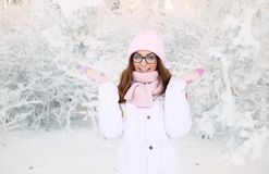 Adorable happy young blonde woman in pink knitted hat scarf having fun snowy winter park forest in nature Stock Photo