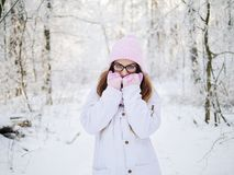 Adorable happy young blonde woman in pink knitted hat scarf having fun strolling snowy winter forest in nature Royalty Free Stock Photos