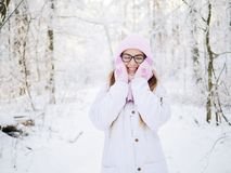Adorable happy young blonde woman in pink knitted hat scarf having fun strolling snowy winter forest in nature Stock Photos