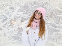 Adorable happy young blonde woman in pink knitted hat scarf mittens having fun snowy winter park forest sunny day in nature Stock Photos